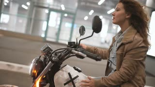 Beautiful young woman riding an old cafe racer motorcycle on street. Female biker at night city
