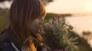 beautiful young woman with a bouquet of wildflowers on the coast at sunset
