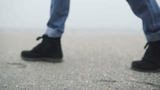 Close up of legs of a young hipster man or woman in mustard trousers and black stylish shoes walking alone on the beach.