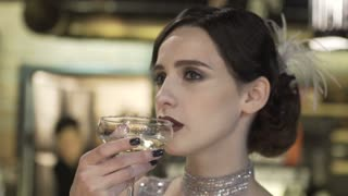 Close-up portrait of a young attractive woman in a 1920s style drink wine or champagne at the bar. Model with a beautiful make-up