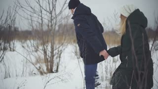 couple of lovers walk through deep snow and drifts in the field