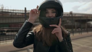 Cute young brunette woman and motorcycle helmet