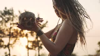 Hippie attractive woman dances and conjures with a human skull. Woman in the image of a witch at sunset or sunrise