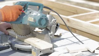 Man hard worker cutting wooden floor by electric saw in work place