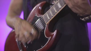 Man lead guitarist playing electrical guitar on concert stage