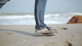 Man legs in jeans running on the beach