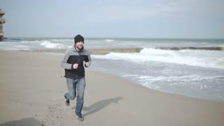 man runs around the sea, on an abandoned beach
