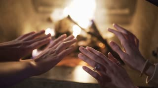 people are warming their hands by the fire at home