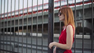 Portrait of attractive young red-haired woman on street in red dress, having a good time at sunset. Slow motion