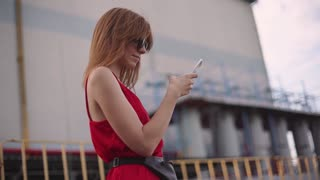 Portrait of attractive young red-haired woman on street in red dress use smartphone. Slow motion