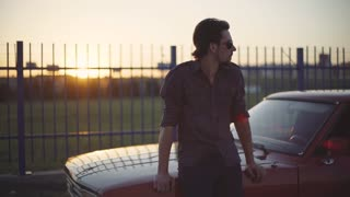 Portrait of handsome man with his old classic powerful car on street, at sunset or sunrise