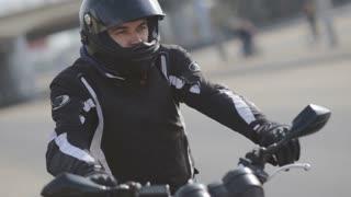 portrait of young attractive motorcyclist with black helmet on street. Man motorcycle biker