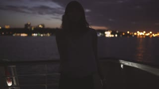 silhouette of a young attractive woman against a background of a night city aboard a boat