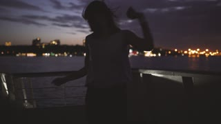 Silhouette of a young happy girl feeling awesome and dance on the ship at dark night. Woman having fun time