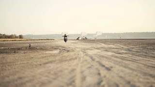 Two beautiful girlfriends ride without hands on a motorcycle on desert at sunset. Female biker. Slow motion