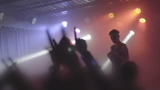 Two beautiful young women DJ play the music on the mixing console in the nightclub. Against the background of unrecognizable people. Slow motion
