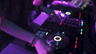 Two beautiful young women DJ play the music on the mixing console in the nightclub