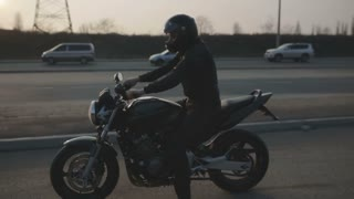 young attractive man motorcyclist with black helmet and sport motorcycle on street