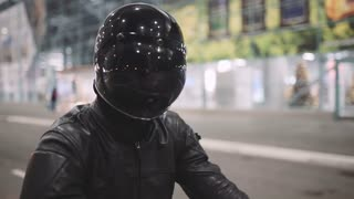 young attractive man motorcyclist with his helmet and custom motorcycle on night street