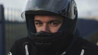 young attractive motorcyclist with black helmet on street. Man motorcycle biker