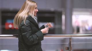 young beautiful woman alone drinks whiskey alcohol from flask in shopping mall