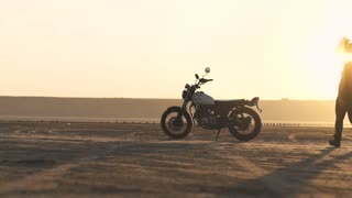Young beautiful woman goes to her old cafe racer motorcycle, sits on it and makes a burnout, then rides away. Female motorcycle rider.