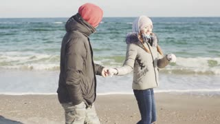Young man and woman walking on the beach. Couple on sea at cold winter day