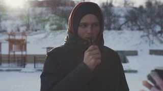 Young man vaping outside in good sunny winter weather. Man smoking electronic cigarette. Slow motion