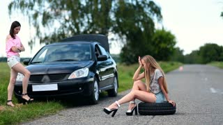 Annoyed woman sitting on spare wheel on the road