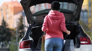 Back view of woman putting shopping bags in car