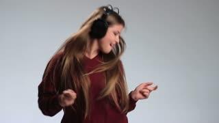 Beautiful female dancing to music in headphones