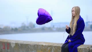 Beautiful sad blond woman with violet balloon