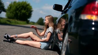 Blonde girl sitting on road near her broken car