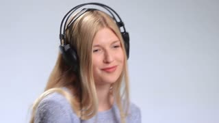 Blonde girl with headphones listening to music