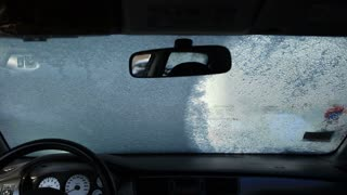 Cleaning car window with an ice scraper