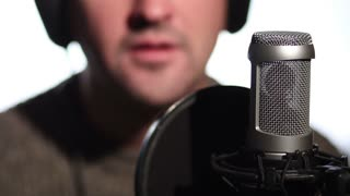 Close up man singing into a condenser microphone