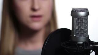 Closeup female singer recording track in studio