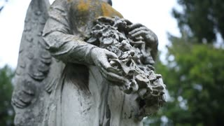 Closeup statue of angel holding wreath at cemetery
