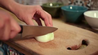 Closeup woman hands slicing onion on cutting board