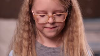Cute little girl in glasses smiling