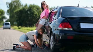 Cute woman jacking up her car to change flat tire