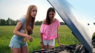 Cute women standing near opened hood of broken car