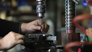 Drilling hole in iron piece with auger in workshop