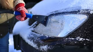 Driver scraping ice from car headlight in winter
