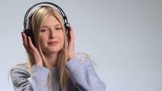 Emotional girl enjoying music in headphones