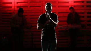Emotional singer singing on illuminated stage