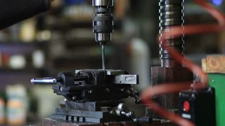 Employee drilling hole in flat steel plate