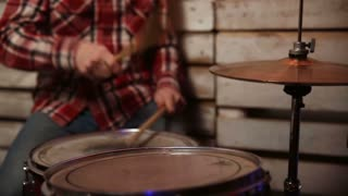 Expressive drummer playing at drums with drumstick