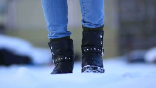 Female feet in black leather winter shoes in snow