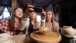 Female friends taking food picture with smartphone